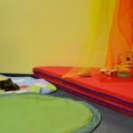 Bild: Kuschelecke - rote Matratzen mit bunten Kissen und darüber herabhängenden Tücher. Davor Krabbeldecken mit Spielzeug.