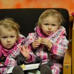 Bild: Zwilinge sitzen nebeneinander auf einem Stuhl. Kind links winkt, Kind rechts ißt Kuchen