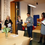 Bild: 6 Workshopteilnehmer stehen im Halbkreis und beraten sich, jeweils mit einem Faltblatt des Familienzentums in der Hand