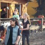Bild: Zwei Mädchen führen ein Ponny auf dem ein Junge sitzt