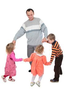 Bild: Mann tanzt mit 3 Kindern im Kreis