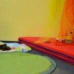 Bild: Die Krabbelecke mit roten Matratzen und bunten Schleiern darüber hängend. Im Vordergrund eine grüne und bunte runde Decke mit Spielzeug