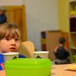 Bild: kleiner Junge sitzt bei Kaffee und Keksen am Tisch und schaut in die Kamera, im Hintergrund spielen Kinder auf dem Fußboden