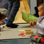 Bild: kleines Kind spielt auf dem Fußboden mit Holztäfelchen