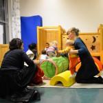 Bild: Junge Mütter spielen mit ihren Kleinkindern auf einer Krabbelburg