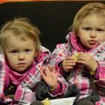 Bild: Zwillingsmädchen sitzen nebeneinander auf einem Stuhl und grüßen