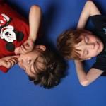Bild: 2 Jungs liegen Kopf an Kopf auf blauem Hintergrund
