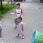 Bild: 2 Kleinkinder und ein Junge mit Boule-Kugeln auf der Strasse