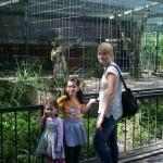 Bild: Mutter mit ihren 2 Töchtern vor dem Käfig