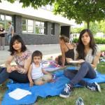 Bild: Zwei Mädchen und ein kleiner Junge sitzen auf eine Decke auf der Wiese und essen
