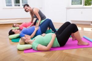 Bild: 3 Frauen machen Rückenübungen auf dem Boden leigend unter Anleitung