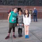 Bild: 3 Mädchen stehen am Fuß der Siegesäule und blicken in die Kamera