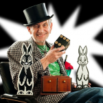 Bild: Zauberer mit Zylinderhut auf einem Stuhl sitzend, mit zwei Hasen aus Pappe auf dem Schoß und einem Würfel in der Hand. Weißer Stern im Hintergrund.