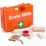 Bild: Erste Hilfekasten mit Pflaster und Schere im Vordergrund