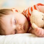 Bild: schlafendes Kind mit Teddybär unterm Arm