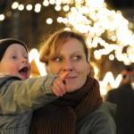 Bild: Mutter mit Kind auf dem Arm auf einem Weihnachstmarkt