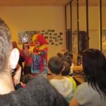 Bild: ein Clown agiert im Hintergrund. Kinder von hinten im Vordergrund