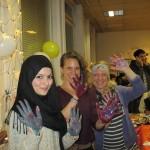 Bild: 3 junge lachende Frauen des Teams strecken ihre innenseitig bemalten Hände zum Betrachter