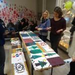 Bild: die Leiterin und das Team betrachten die gemalten Weihnachtsbaumbilder der Kinder auf einem Tisch