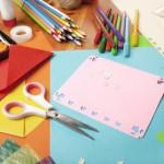 Bild: Blick auf Tisch mit buntem Bastelzeug - Schere, Tuschkasten, Bunt- und Filzstifte, buntes Papier