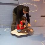 """Bild: Kind sitzt auf einer an einem Seil """"fahrenden"""" Wolke, die von der Mutter gezogen wird"""
