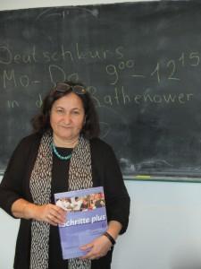 Bild: Lehrerin steht mit Lehrbuch in der Hand vor der Tafel