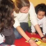 Bild: Kinder und Erzieherin beim Geschichten lesen knieend auf dem Fussboden, ein Buch in der Mitte