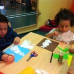 Bild: Kinder sitzen basteln am Tisch