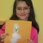 Bild: Mädchen hält ein Bild mit einem Schneemann aus Watte
