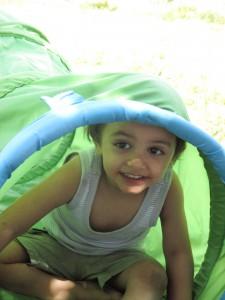 Bild: Kind guckt aus einem Spieltunnel heraus