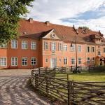 Bild: Herrenhaus - rotes doppelstöckiges Haus mit Koppelzaun im Vordergrund