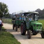 Bild: Kinder und Erwachsene fahren in einem grünen Traktor mit Anhänger