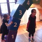 Bild: zwei Kinder spielen an einem aus großen Bauklötzern zusammangesetzten Torbogen