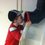 Bild: Junge ruft in eine Regenabwasserroh an der Wand