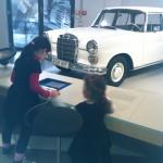 Bild: zwei Kinder vor einem Ausstellungsstück Auto