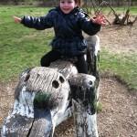 Bild: Junge sitzt freihändig auf einem großen Holzhund