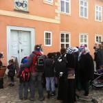 Bild: Die Besuchergruppe des FZ versammelt sich vor dem orang-farbenen Herrenhaus und die Leiterin hält eine Rede