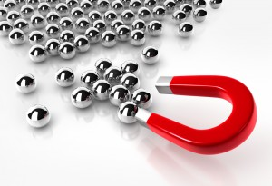 Bild: roter Hufeisenmagnet zieht silberne Stahlkugeln auf einem Tisch an