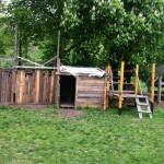Bild: eine Holzhütte auf einer Wiese