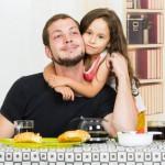 Bild: Mädchen umarmt ihren Vater von hinten am Frühstückstisch