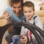 Bild: Vater und Sohn spielen begeistert Autorennbahn - Looping mit kopfüber fallenden Rennauto im Vordergrund