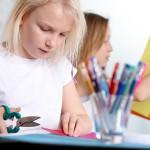 Bild: zwei Mädchen sitzen am Tisch und basteln