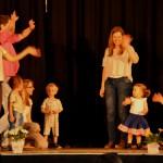 Bild: Kinder und Eltern winkend auf einer Bühne