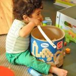 Bild: Kind sitzt vor einem großen Bauklotzeimer und beißt in den Henkel
