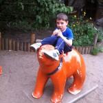 Bild: Kind sitzt essend auf einem Berliner Bär Skulptur