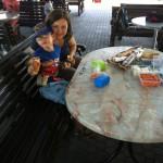 Bild: Sylvia und Benjamin machen Pause, sitzend am Tisch mit Lebensmitteln und essen. Blick zum Betrachter.