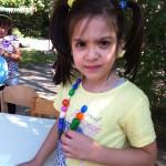 Bild: Mädchen zeigt stolz ihre selbst gebastelte Kette und blickt Betrachter an
