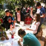 Bild: 7 Kinder basteln und malen an einem Tisch im Freien