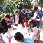 Bild: 8 Kinder basteln und malen an einem Tisch im Freien