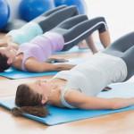 Bild: 3 Frauen liegen auf dem Rücken mit angehobenem Po auf Yogamatte